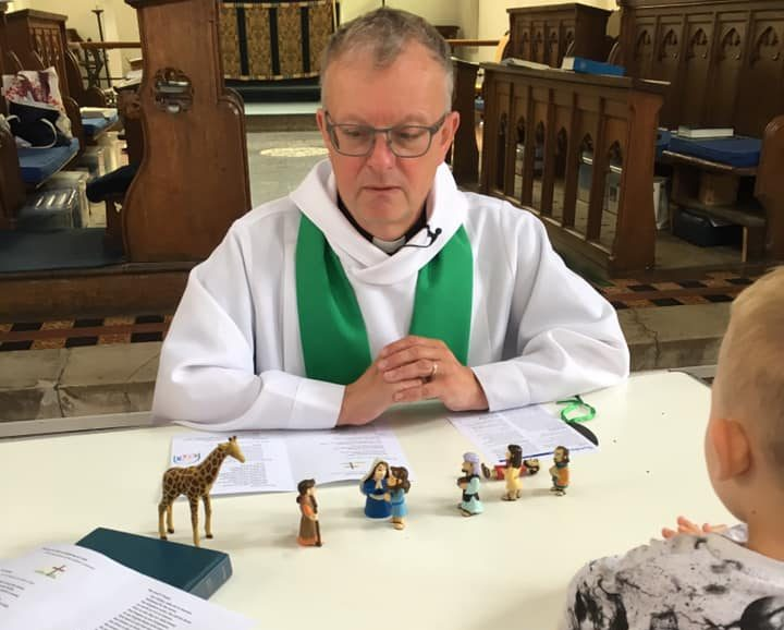 Rev Quentin using toy figures to tell a sermon to children